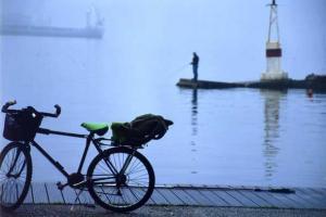 ποδήλατο σε λιμάνι με φόντο ένα ψαρά και ένα φάρο