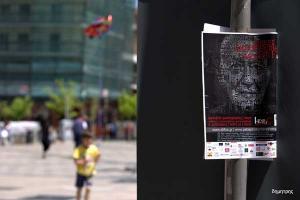φωτογραφία μίας αφίσας του φεστιβάλ και στο background ένα παιδί που τρέχει