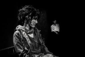 νεαρός άντρας καθιμσένος στο βάθος κοιτάει μία ώριμη κυρία