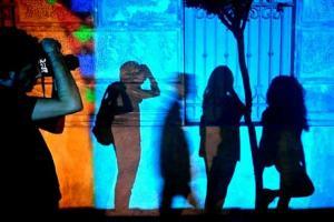 Φωτογράφος φωτογραφίζει τη σκιά του και τρεις άλλες σκιές σε τοίχο κτηρίου με μπλε φόντο