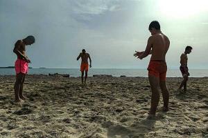 τέσσερις άνδρες με κοντά μαγιό σε παραλία με άμμο καλοκαίρι