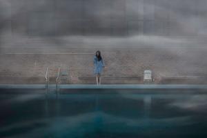 γυναίκα με μπλε φόρεμα στέκεται στην άκρη μιας θερμαινόμενης πισίνας