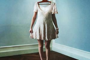 φωτογραφία μίας κοπέλας που φορά ένα κοντό ρόζ φόρεμα και στη θέση του κεφαλιού της είναι μία κρεμάστρα