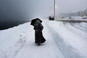 γυναίκα ντυμένη στα μαύτα περπατάει σε χιονισμένο δρόμο
