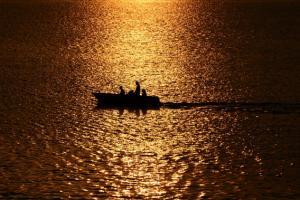 βάρκα σε θάλασσα στη δυση του ηλίου