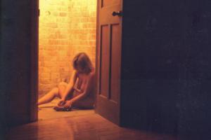 """Ενότητα 2 φωτογραφιών-τεκμηρίωση της περφόρμανς """"Charlie"""" / γυμνή γυναίκα κάθεται στο πάτωμα δίπλα σε ανοιχτή πόρτα"""